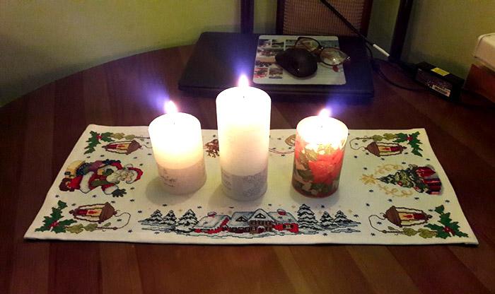 вышитая новогодняя дорожка, на которой стоят свечи, вид сбоку