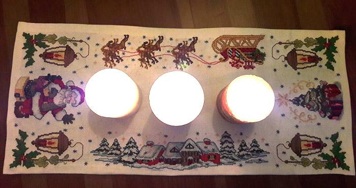 вышитая новогодняя дорожка, на которой стоят свечи, вид сверху